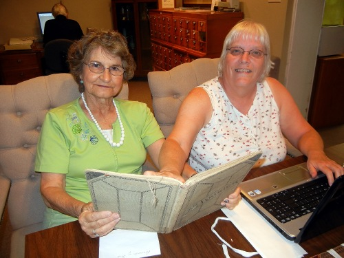 Evelyn Wekke and Billie Todd work on another volume of the Grant Funeral Home Books