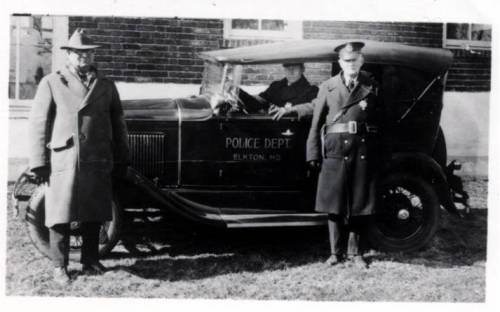 The Elkton Police Department acquired this patrol car, in the late 1920s. (L to R  Mayor Taylor McKenney, the night officer, and Chief Potts).  This was the first county or municipal police vehicle in Cecil.