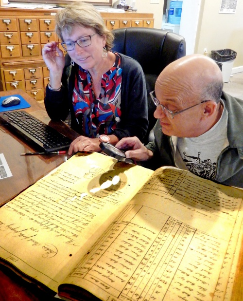 Jo Ann and Tom examine a page of tax records.