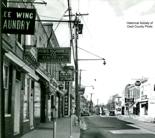 A few decades into the 20th century, the E. Main St. hangs in front of Lee Wing Laundry.  This location is opposite the present day county courthouse.  Source:  Historical Society of Cecil County.