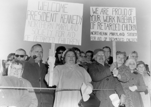 Residents hold signs greeting President Kennedy.