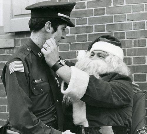 Elkton Police Officer (in uniform) greets old Saint Nick.  Officer Jim Long is dressed as Santa.